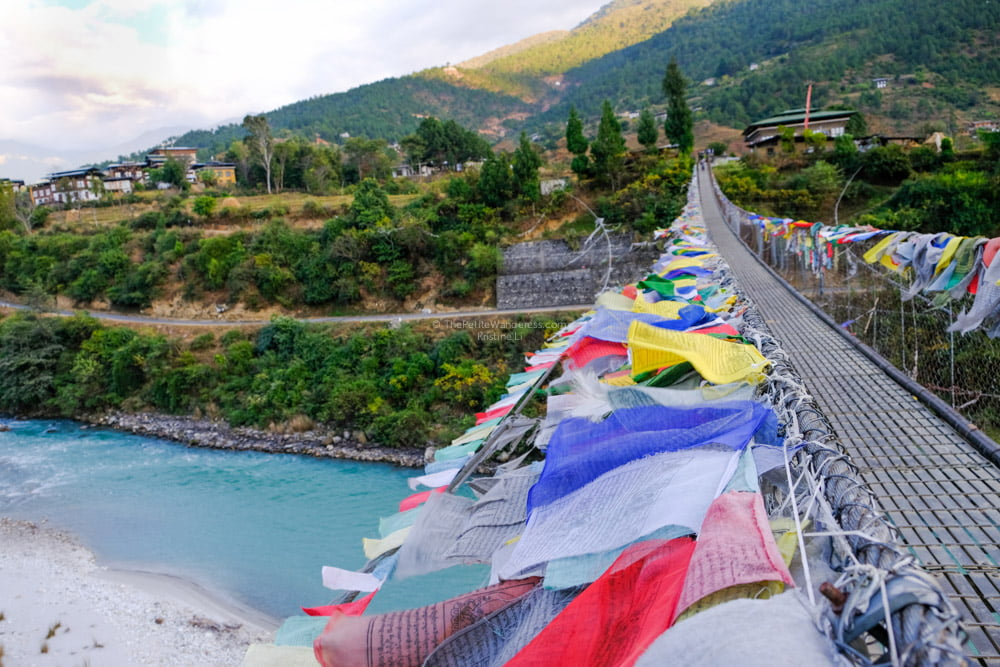 prayer flags along Bhutan's longest suspension bridge | Bhutan in December – It Might be the Best Time to Visit Bhutan • The Petite Wanderess