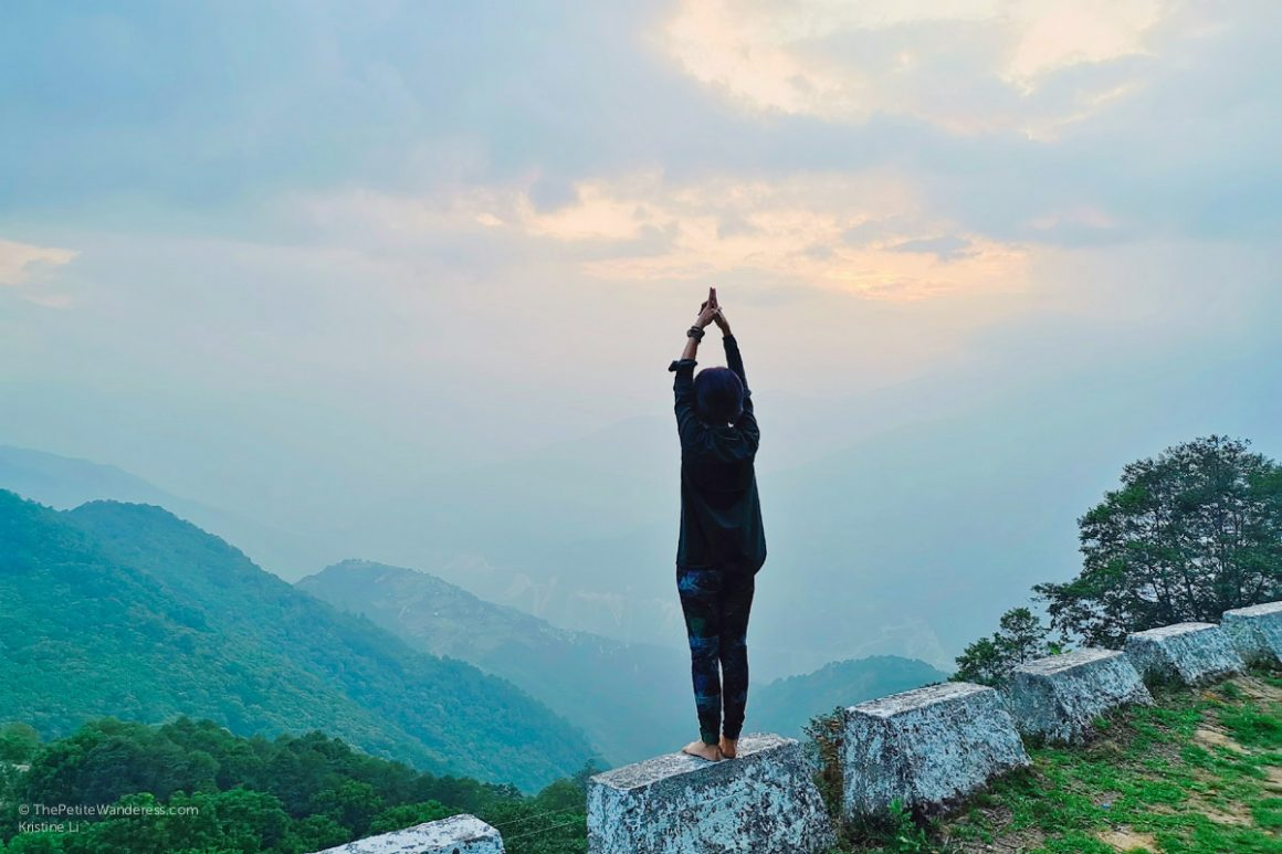 Mountain yoga pose with hands stretched up | Eastern Bhutan road trip photos • The Petite Wanderess