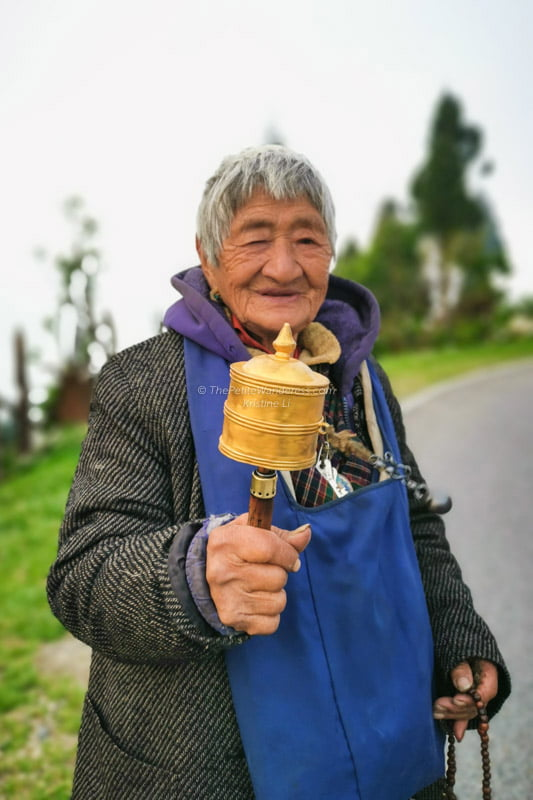 old Bhutanese lady holding portable prayer wheels | Eastern Bhutan road trip • The Petite Wanderess